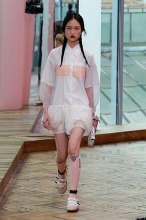 A white shirt dress with knee-high socks and Prada's statement plaits.
