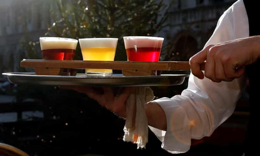 A waiter in Brussels carries glasses of Belgian beer