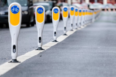 Row of bollards separating a cycle lane from cars.