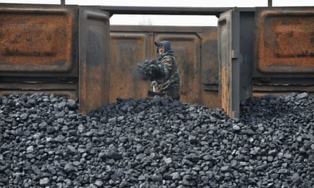 A worker unloads coal at a storage site in Shenyang, China. The report by coal industry executives claims coal is not the cause of China's air quality problem.