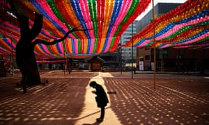 A Buddhist believer wearing a face mask to prevent contracting the coronavirus disease prays under colourful lanterns ahead of the upcoming birthday of Buddha at a temple in Seoul, South Korea, March 25, 2020.