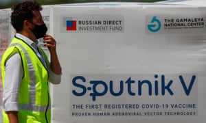 Airport worker in Buenos Aires standing next to boxes of Sputnik V Covid vaccine