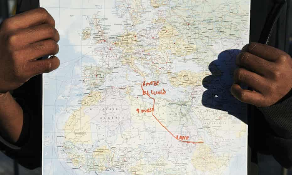 Abrahm from Eritrea, who is 17 years old, holds up a map showing his route to Italy
