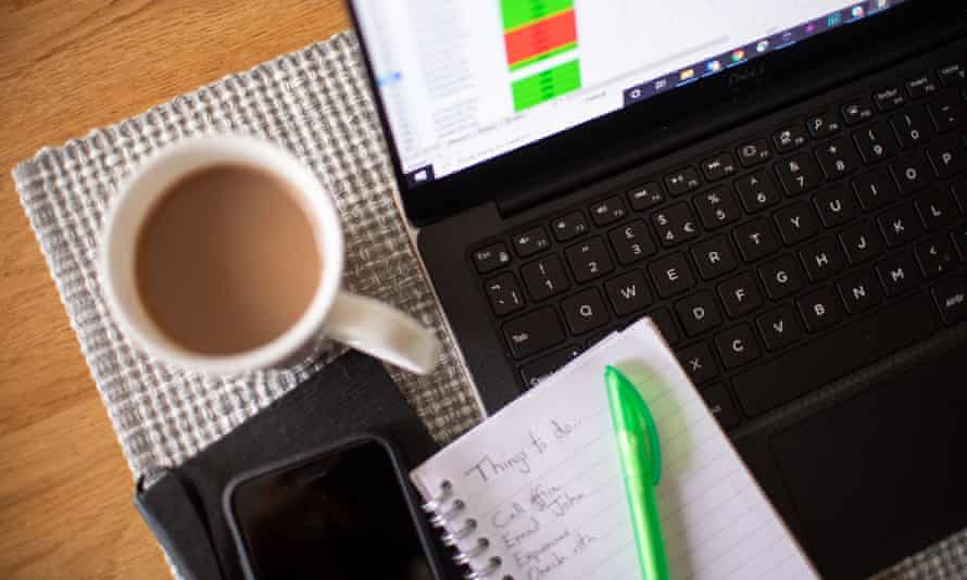 A laptop, notepad, cup of tea and a phone on a desk