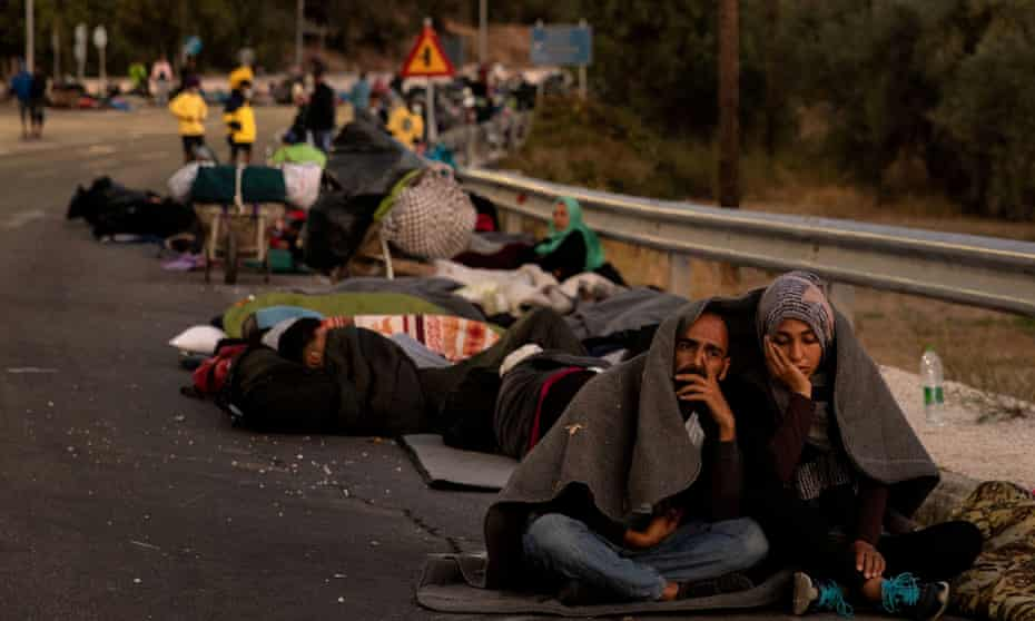 Refugees camp on a road following the fire at the Moria camp on Lesbos