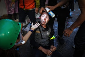 People assist a woman who was exposed to teargas by pouring milk over her face after police fired teargas and water canon to try and disperse protesters outside parliament in Bangkok.