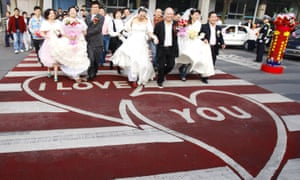 "Newlyweds cross over a ""Love Zebra Crossing"" on Valentines Day in Chengdu"