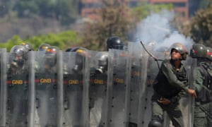Member of the National Guard throws an object towards opposition supporters on Wednesday.