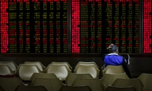 An investor monitors stock prices at a brokerage house in Beijing