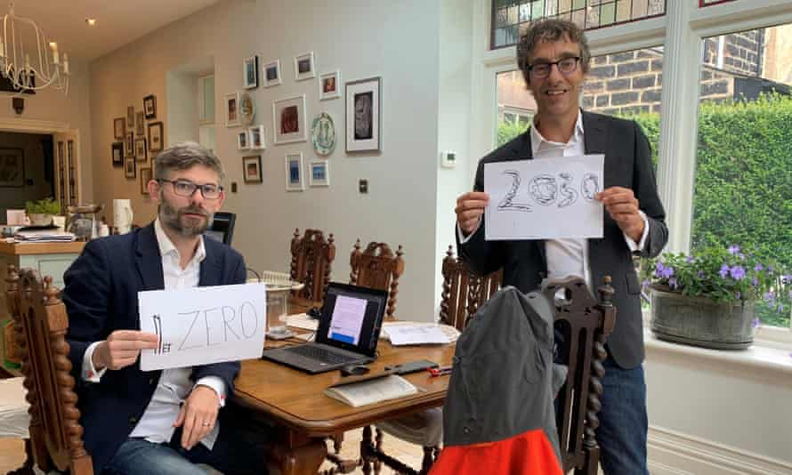 The scientists Joeri Rogelj and Piers Forster hold up signs urging a reduction in carbon emissions, after completing the major UN climate report
