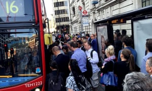 People queue to get on a bus outside Victoria station.