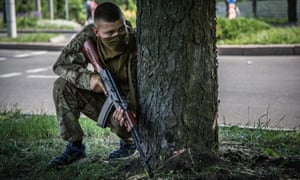 A pro-Russia militiaman taking cover as Ukrainian troops attack rebels at Donetsk international airport.