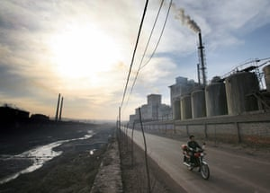 A cyclists passes in front of a factory in the Chinese town of Yangquan.