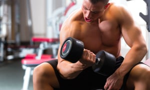 Bodybuilder seated in a gym and lifting a dumbbell