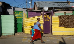 A mother walks her children to school in the Alexandra township of Johannesburg
