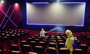 Workers disinfect a cinema hall in Kolkata following government's permission to reopen cinemas on 15 October.