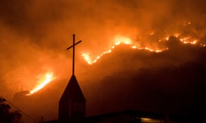 Flames from a wildfire advance on a church in California