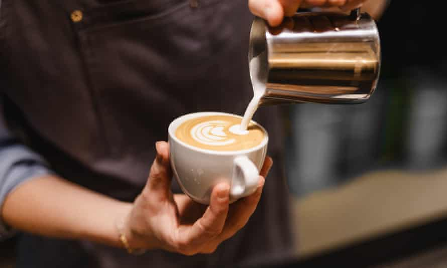 a barista pours a frothy coffee