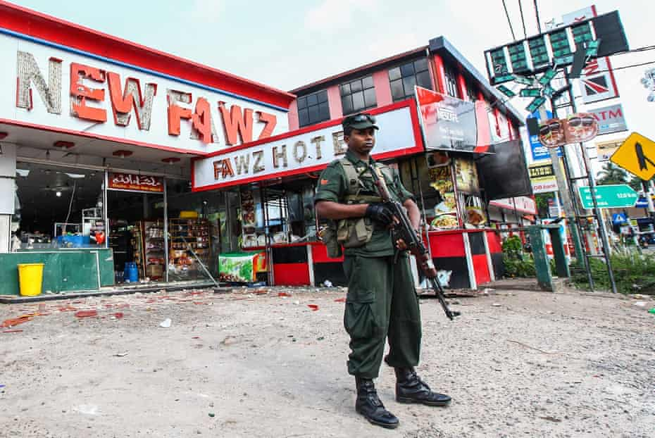 A security force member guards damaged shops after mobs attacked Muslim-owned businesses in Gampaha, north of Colombo, in May.