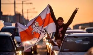 Demonstrators in cars in Minsk hold aloft Pahonia flag, a patriotic emblem of Belarus