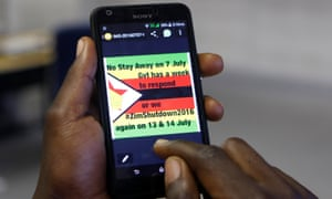 A man checks a message on his mobile phone, in Harare, 7 July 2016.