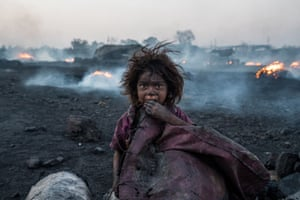 A child engulfed by plumes of smoke from burning coal inside an unregulated charcoal production field