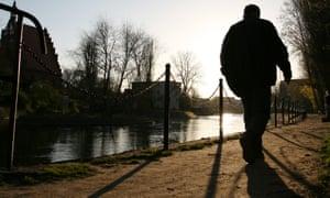 Elderly man walking by a canal