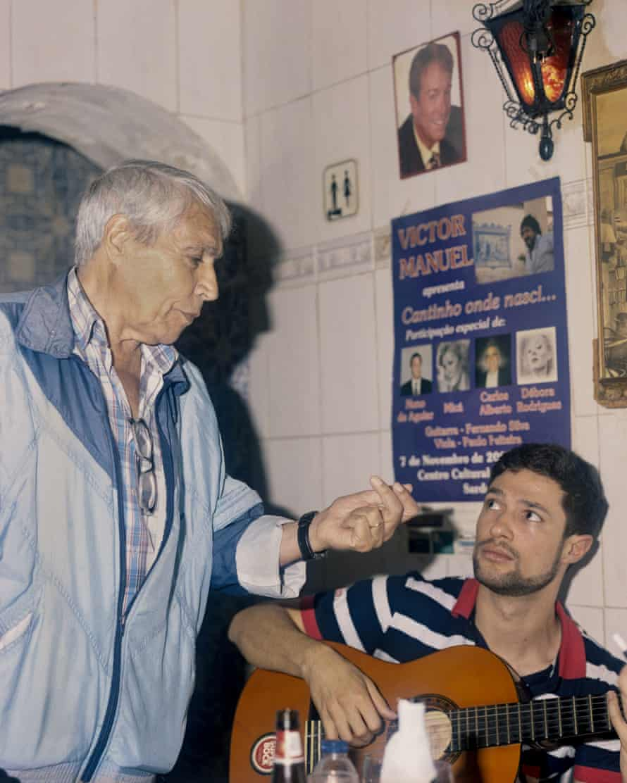 Manuelo gives advice to a less experienced fadista at the fado house.