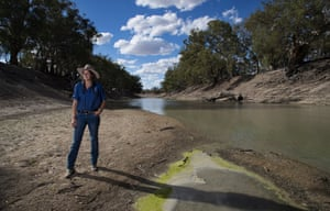 Kate McBride stands on the banks of the Darling river, which flows past her family home, Tolarno. The waterholes are changing colour thanks to blue-green algae