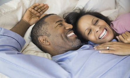 Cheerful couple resting in bed