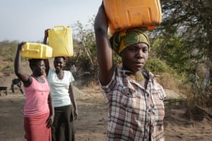 Never Rukia, 28, from Uganda (foreground) with Mary Kiden, 17, and Christin Awate, 16, from South Sudan collect water at Bidi Bidi