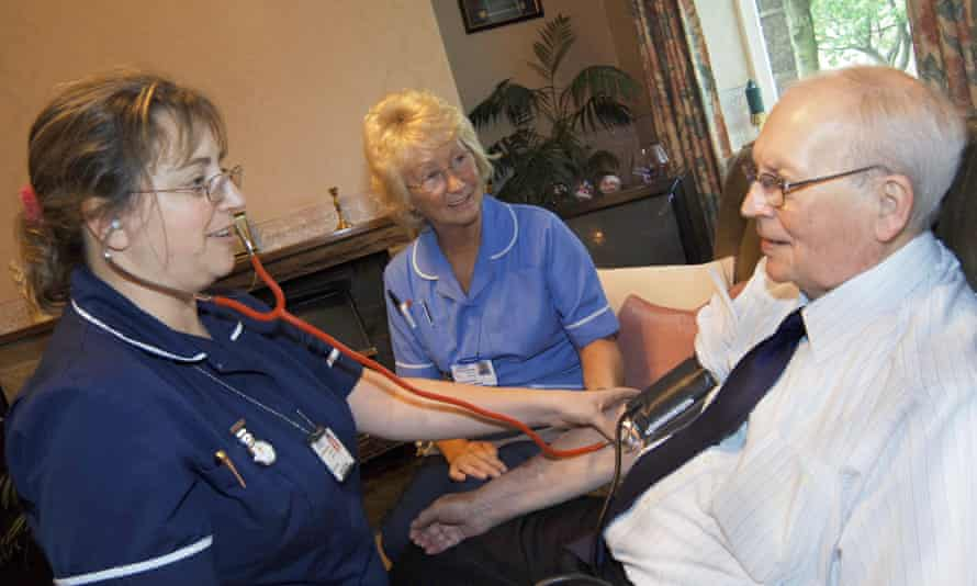 A discharged elderly patient is visited in his home by district nurse and health support worker to check his blood pressure Bradford, Yorkshire