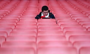 An Arsenal fan studies the match day programme inside the stadium before the start.