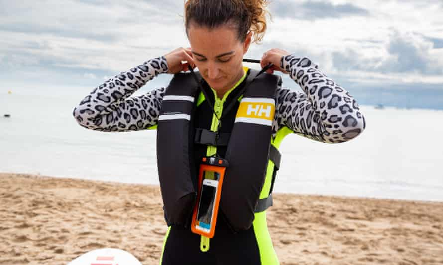 Stand up paddleboarders (SUP) checking and preparing their equipment before going for a paddle at Swanage beach. Mobile phone in waterproof pouch. Sea safety
