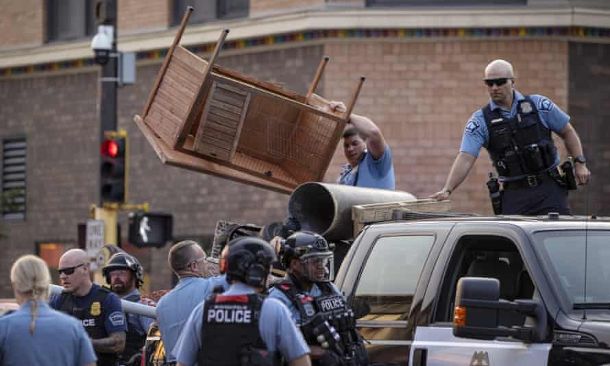 Police clear out items used to barricade Lake Street in the Uptown neighborhood of Minneapolis, on Wednesday. A St Paul man was charged with murder after allegedly driving into a group of protesters.
