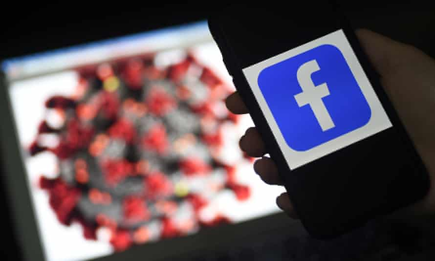 The Facebook logo is displayed on a mobile phone screen photographed on coronavirus illustration