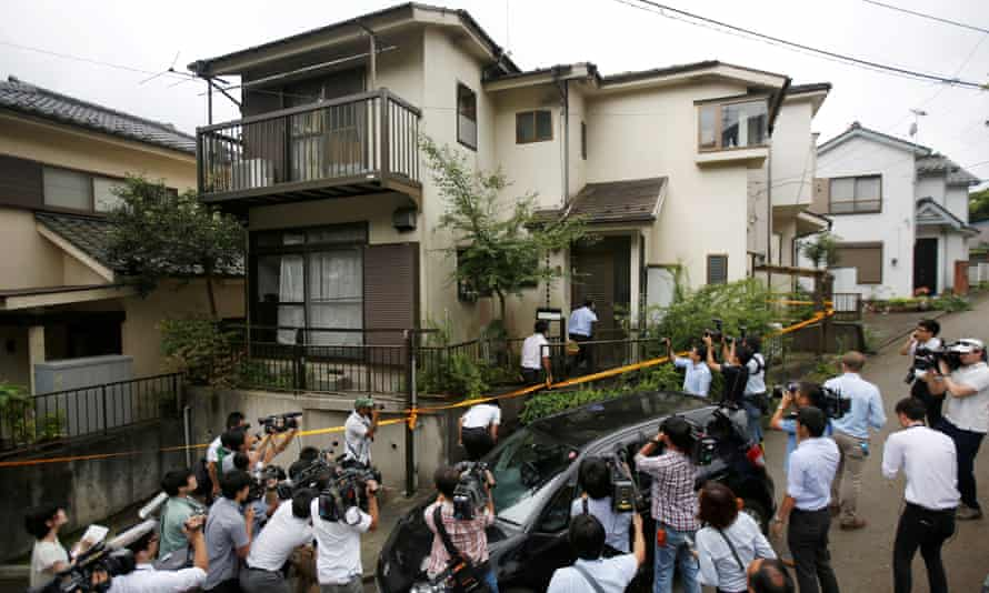 Members of the media crowd outside as police officers raid the house of Satoshi Uematsu in Sagamihara, Japan.