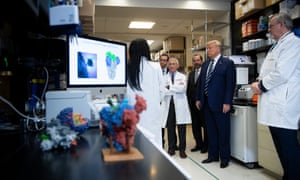National Institute of Allergy and Infectious Diseases Director Anthony Fauci (C) looks on next to Donald Trump during a tour of the National Institutes of Health's Vaccine Research Center in Bethesda, Maryland, on Tuesday.