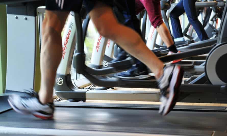 Row of people running on treadmills