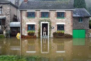 David Arbon has a cup of tea as he looks out of his cottage at floodwater in Lower Lydbrook, where rain from the Welsh hills and high tides have flooded the village