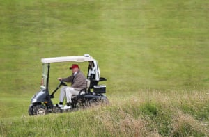 """""""FILE - In this July 31, 2015 file photo, Republican presidential candidate Donald Trump drives his golf buggy during the second day of the Women's British Open golf championship on the Turnberry golf course in Turnberry, Scotland. Trump wants to build another huge wall, this time to keep out the rising seas threatening to swamp his luxury golf resort in Ireland. He has called climate change a """"con job"""" and a """"hoax."""" But in a permit application filed earlier this month in County Clare, Ireland, the Trump International Golf Links and Hotel is seeking permission to build a two-mile-long stone wall between it and the Atlantic Ocean. (AP Photo/Scott Heppell, File)"""""""