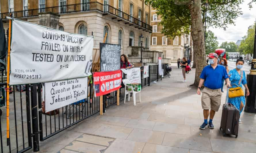 People walk past anti-vaccination protesters in Westminster