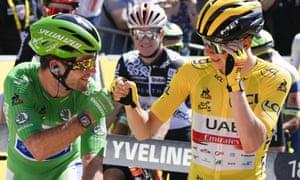Slovenia's Tadej Pogacar, wearing the overall leader's yellow jersey, greets Britain's Mark Cavendish, wearing the best sprinter's green jersey.