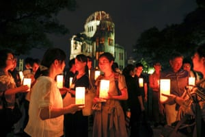 People holding candles gather for the Peace Candle vigil in front of the Atomic Bomb Dome to comfort soul of victims of the 06 August 1945 atomic bombing at Hiroshima Peace Memorial Park