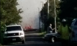 Lava spurts from the ground as emergency vehicles attend the scene.