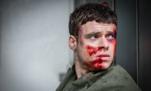 Richard Madden in character as David Budd, who looks concerned while covered in blood