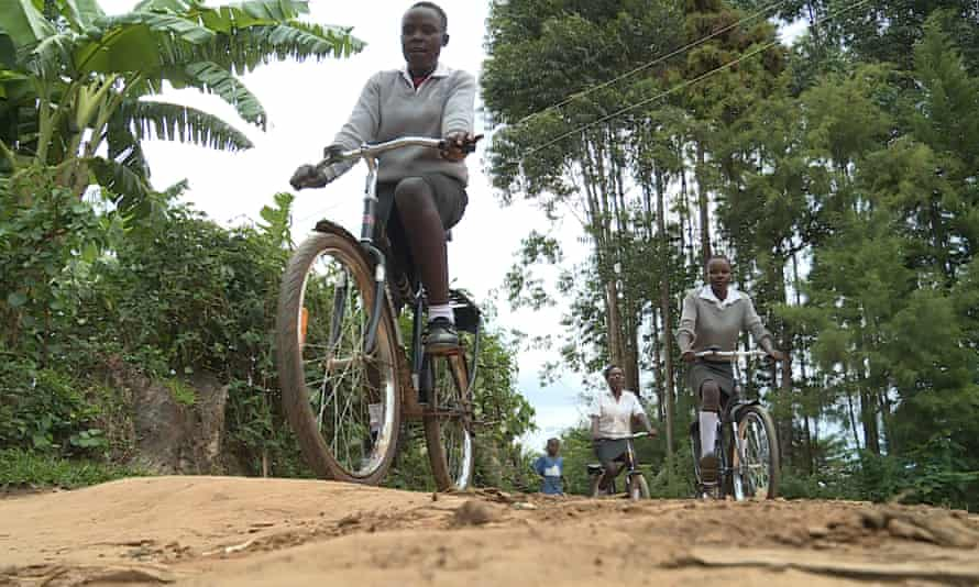 Kenyan school girls riding to school on bicycles