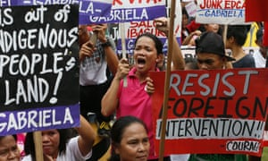 Protesters display placards after forcing their way to the gates of the US embassy in Manila