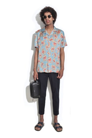 man in blue floral shirt and dark trousers