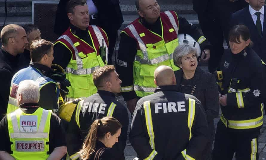 Theresa May speaks to members of the fire service as she visits Grenfell Tower in London on Thursday